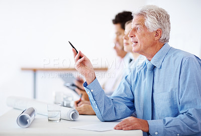 Buy stock photo Male executive raising pen while sitting amongst colleagues during a corporate meeting
