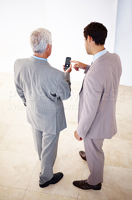 Buy stock photo Rear view of two business men sharing information on cell phone