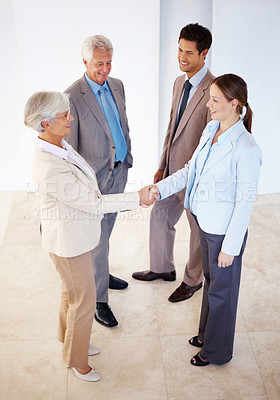 Buy stock photo Portrait of two female executives shaking hands while man smiling at office