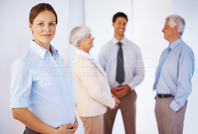 Buy stock photo Portrait of an pregnant woman with group of people talking in background