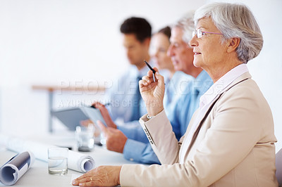 Buy stock photo Portrait of a old  businesswoman paying attention at presentation with colleagues