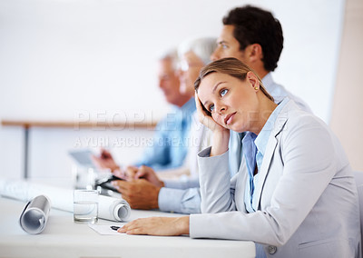 Buy stock photo Beautiful young businesswoman bored at a presentation with her colleagues