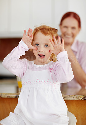 Buy stock photo Portrait of a naughty girl making funny face while a mature woman in blur background