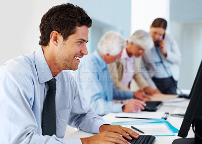 Buy stock photo Portrait of a happy young male business executive using computer with colleagues in back