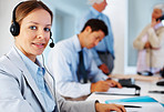 Confident customer care executive with colleagues at back
