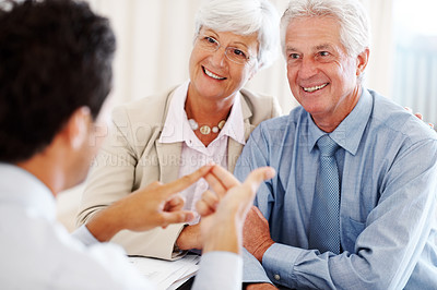 Buy stock photo Portrait of a cheerful old couple discussing financial matter with advisor at office