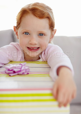 Buy stock photo Closeup portrait of a happy little girl smiling excitedly at the camera while holding a huge gift - copyspace