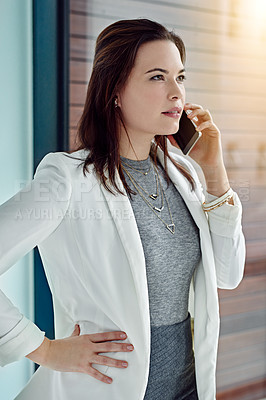 Buy stock photo Shot of a young businesswoman using her phone at work