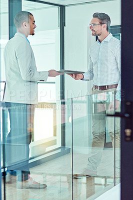 Buy stock photo Shot of a businessman handing a document to a colleague