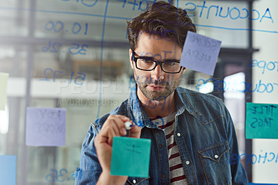 Buy stock photo Cropped shot of a young designer writing notes on a glass wall in a modern office