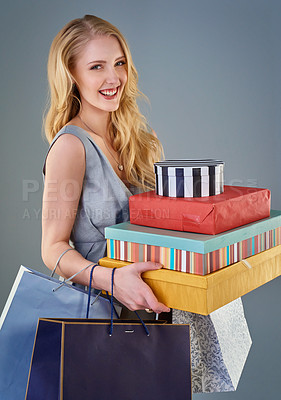 Buy stock photo Cropped studio shot of a happy young woman holding a selection of shopping bags and gift boxes