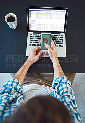 Buy stock photo High angle shot of a young designer using a cellphone in a modern office