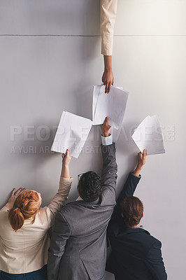 Buy stock photo Cropped shot of businesspeople handing documents to a colleague in an office