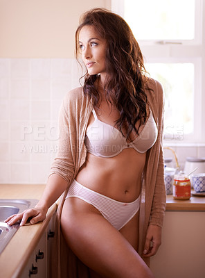 Buy stock photo Shot of a gorgeous young woman posing seductively in her kitchen