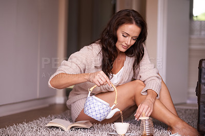 Buy stock photo Shot of a beautiful young woman having tea at home