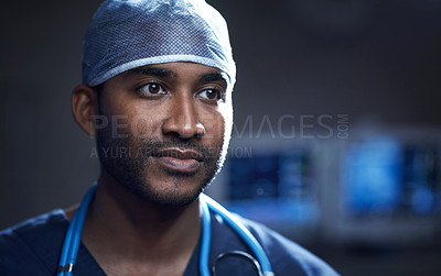 Buy stock photo Shot of a confident young surgeon standing in an operating room
