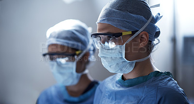 Buy stock photo Shot of a surgeon in an operating room with her assistant in the background