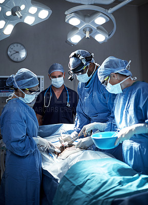 Buy stock photo Shot of a team of surgeons performing a surgery in an operating room