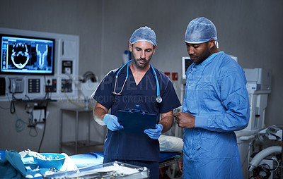 Buy stock photo Shot of two surgeons looking at a patient's file in an operating room
