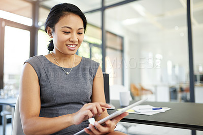 Buy stock photo Cropped shot of a young businesswoman working on a digital tablet in a modern office