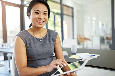 Buy stock photo Portrait of a confident young businesswoman working on a digital tablet in a modern office