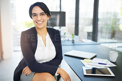 Buy stock photo Portrait of a confident young businesswoman sitting in a modern office