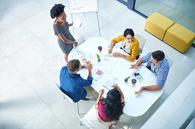 Buy stock photo High angle shot of a group of colleagues meeting in the boardroom