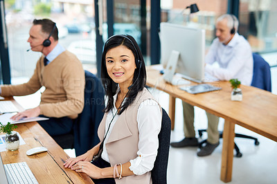 Buy stock photo Cropped portrait of a young businesswoman working in her office with colleagues in the background