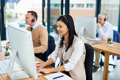 Buy stock photo Cropped shot of a young businesswoman working in her office with colleagues in the background