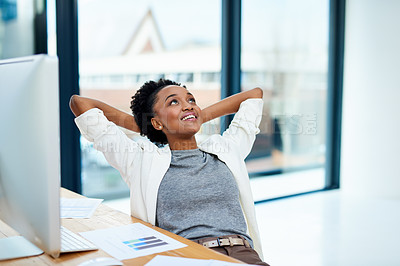 Buy stock photo Cropped shot of a young woman sitting with her hands behind her head in the office