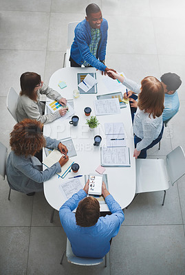 Buy stock photo High angle shot of young businesspeople shaking hands during a meeting