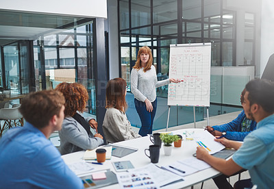 Buy stock photo Shot of a young businesswoman using a whiteboard to give a presentation to her colleagues in a boardroom