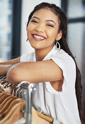 Buy stock photo Cropped portrait of young woman leaning on a clothing rail inside a store