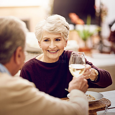 Buy stock photo Shot of an elderly couple toasting with wine glasses while they enjoy a meal at home