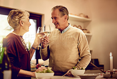 Buy stock photo Shot of an elderly couple chatting and drinking wine together while standing in their kitchen