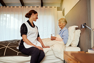 Buy stock photo Shot of a nurse sitting with her elderly patient in her room