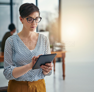 Buy stock photo Cropped shot of a young creative working on a digital tablet in an office