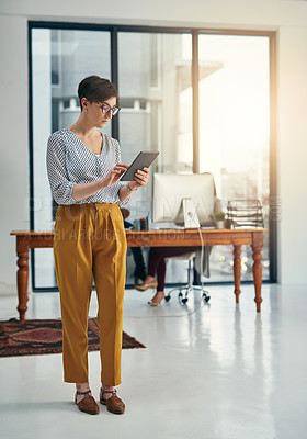 Buy stock photo Shot of a young creative working on a digital tablet in a modern office