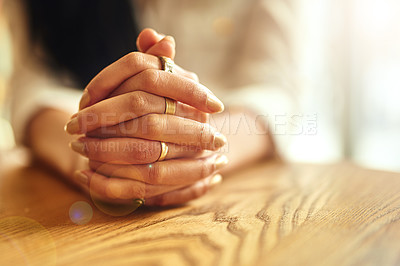 Buy stock photo Closeup of a woman sitting at a table with her hands clasped