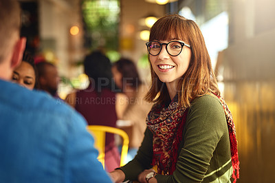Buy stock photo Portrait of a young woman sitting with colleagues having a meeting around a table