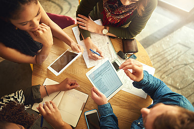 Buy stock photo Shot of a group of coworkers using a digital tablet while having a meeting around a table