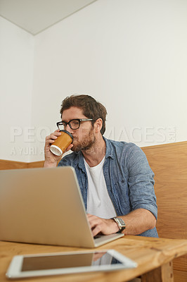 Buy stock photo Cropped shot of a young man drinking coffee while working on his laptop