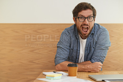 Buy stock photo Cropped portrait of a young man shouting at the camera while sitting at a table
