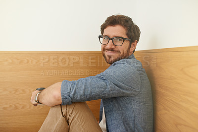 Buy stock photo Cropped portrait of a young man sitting at a table