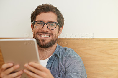 Buy stock photo Cropped portrait of a young man using his digital tablet while sitting at a table