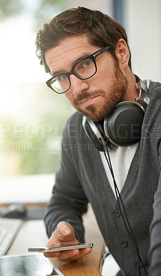 Buy stock photo Portrait of a young entrepreneur using a mobile phone at his work desk