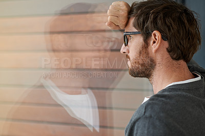 Buy stock photo Shot of a thoughtful young entrepreneur leaning against a glass window in his office