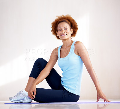 Buy stock photo Portrait of a happy healthy young woman sitting on the floor in gym wear - copyspace