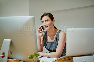 Buy stock photo Shot of a professional businesswoman using a phone at her office desk