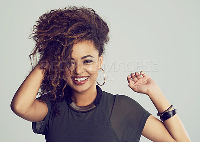 Buy stock photo Studio portrait of an attractive young woman posing against a gray background